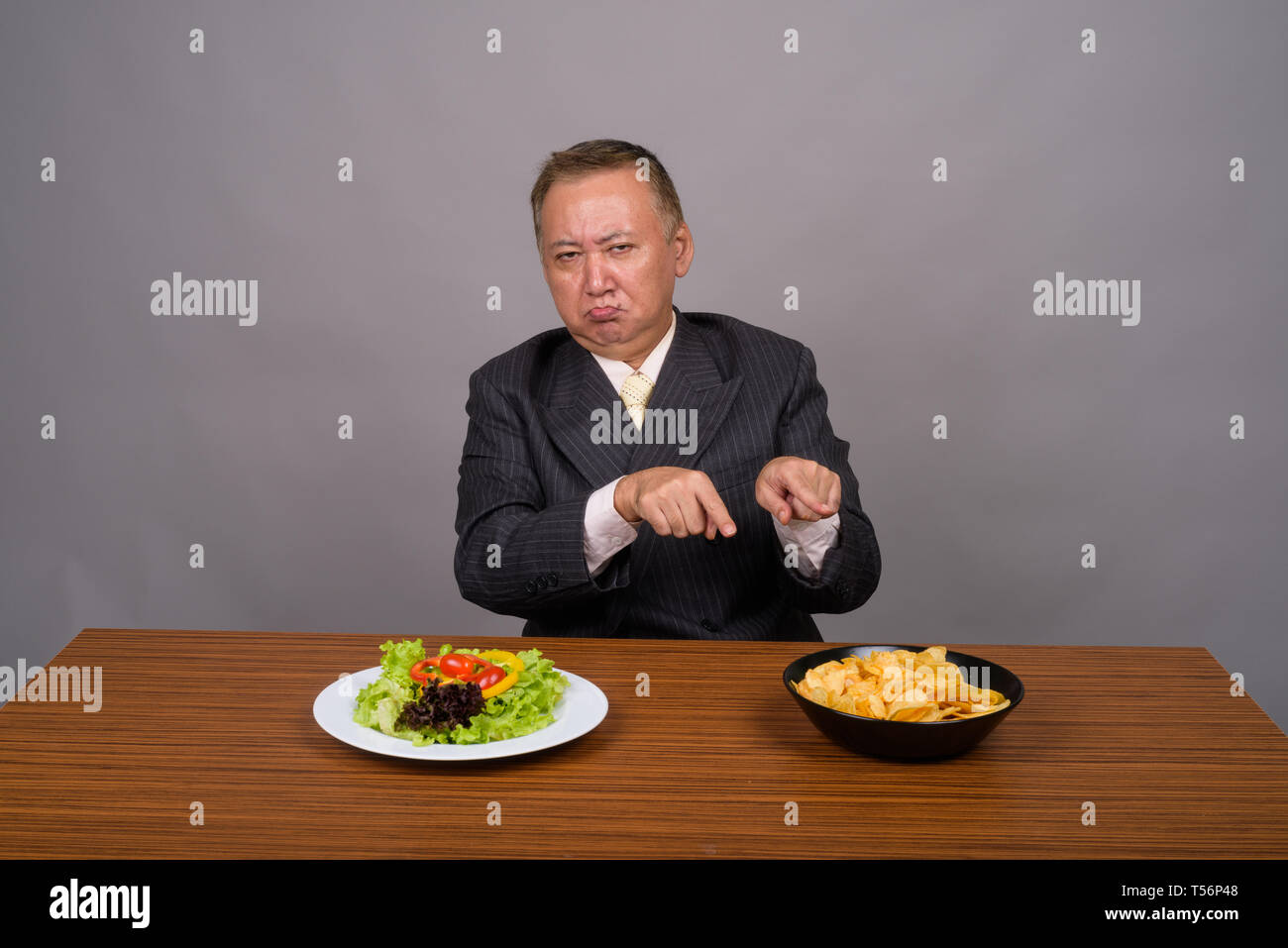 Mature Asian businessman sitting with wooden table against gray  - Stock Image