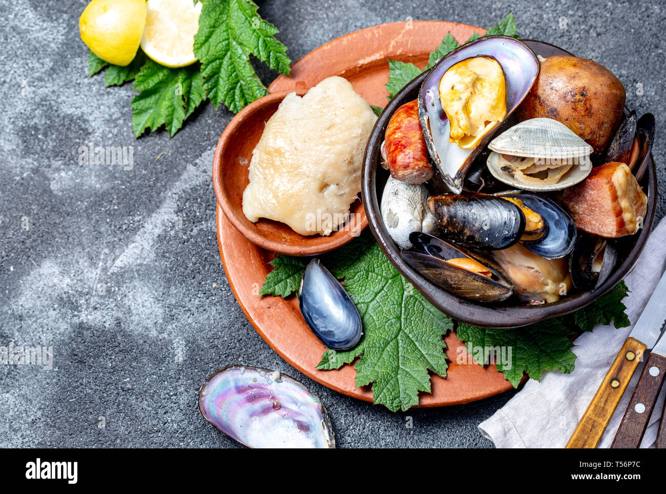 Famous traditional dish of the south of Chile and the Chiloe archipelago - Curanto al Hoyo, Kuranto. Different seafood, meat and potatoes milcao Stock Photo