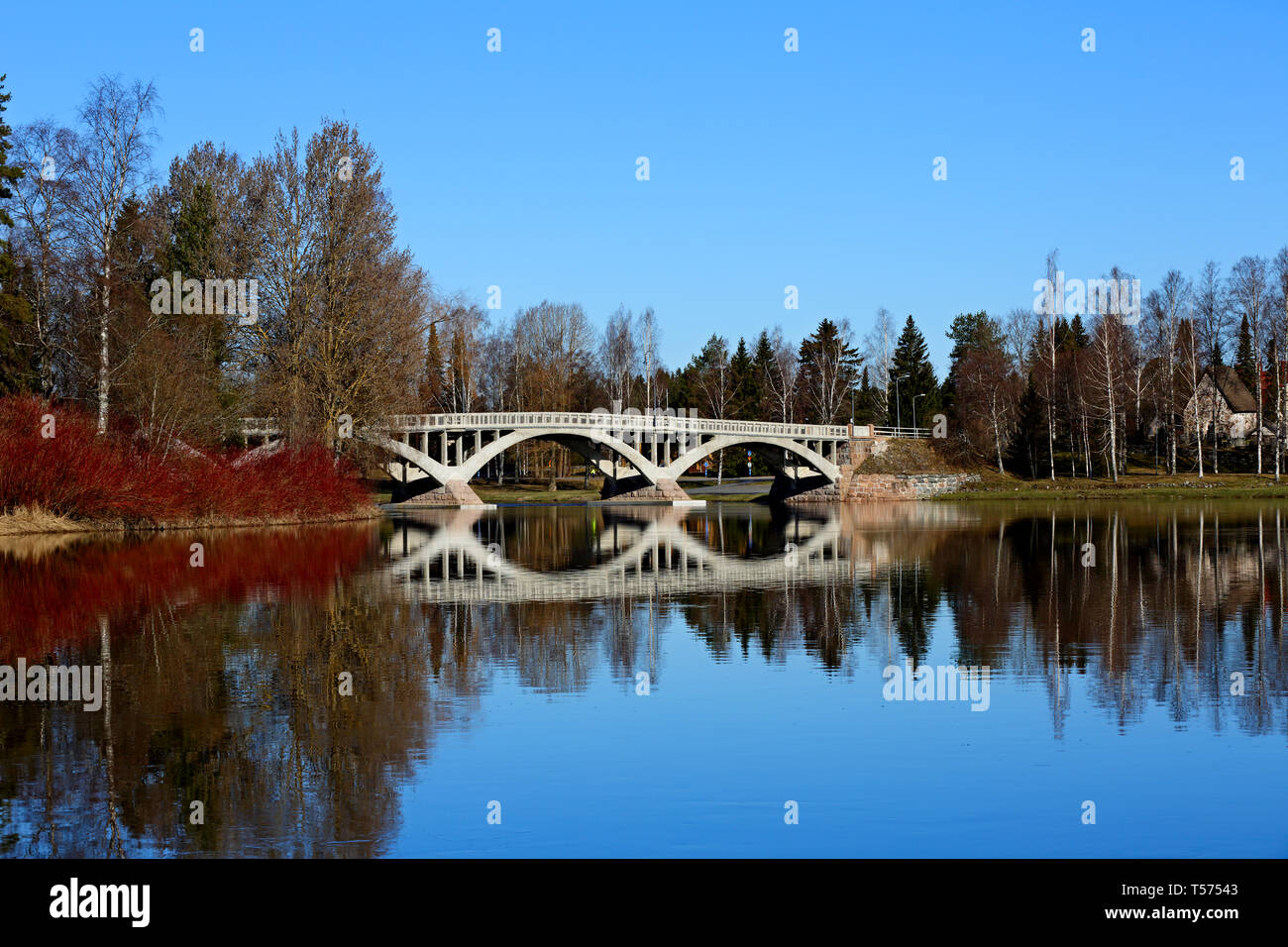 An old grey bridge over a calm river. Clear blue sky is reflecting on a springlike water surface - Stock Image