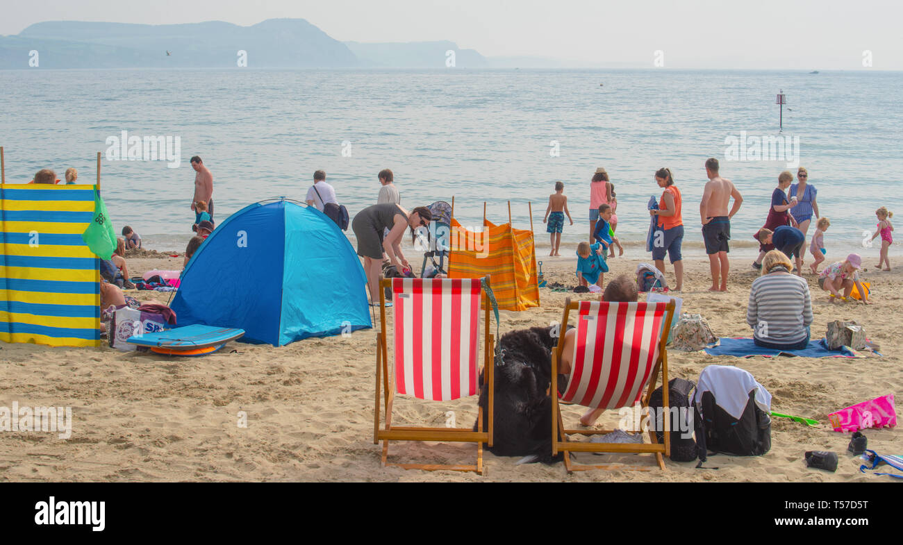 Lyme Regis, Dorset, UK. 22nd April 2019. UK Weather: Holiday makers and beach goers secure a spot early on the pretty beach at the seaside resort of Lyme Regis to enjoy a day of hot and hazy sunshine on the Bank Holiday.  Visitors have enjoyed record breaking heat over the Easter weekend with temperatures set to soar even further today. Credit: Celia McMahon/Alamy Live News. - Stock Image