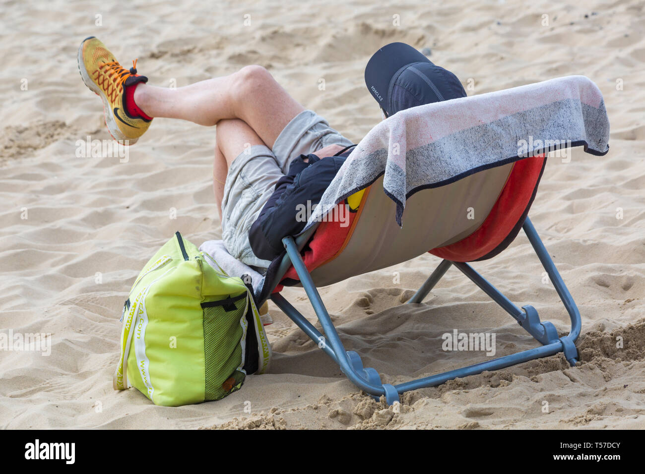 Bournemouth, Dorset, UK. 22nd Apr, 2019. UK weather: after a hazy start the glorious weather continues with hot and sunny weather, as beachgoers head to the seaside to enjoy the heat and sunshine at Bournemouth beaches on Easter Monday before the weather changes and the return to work. Man relaxing in chair on beach. Credit: Carolyn Jenkins/Alamy Live News Stock Photo