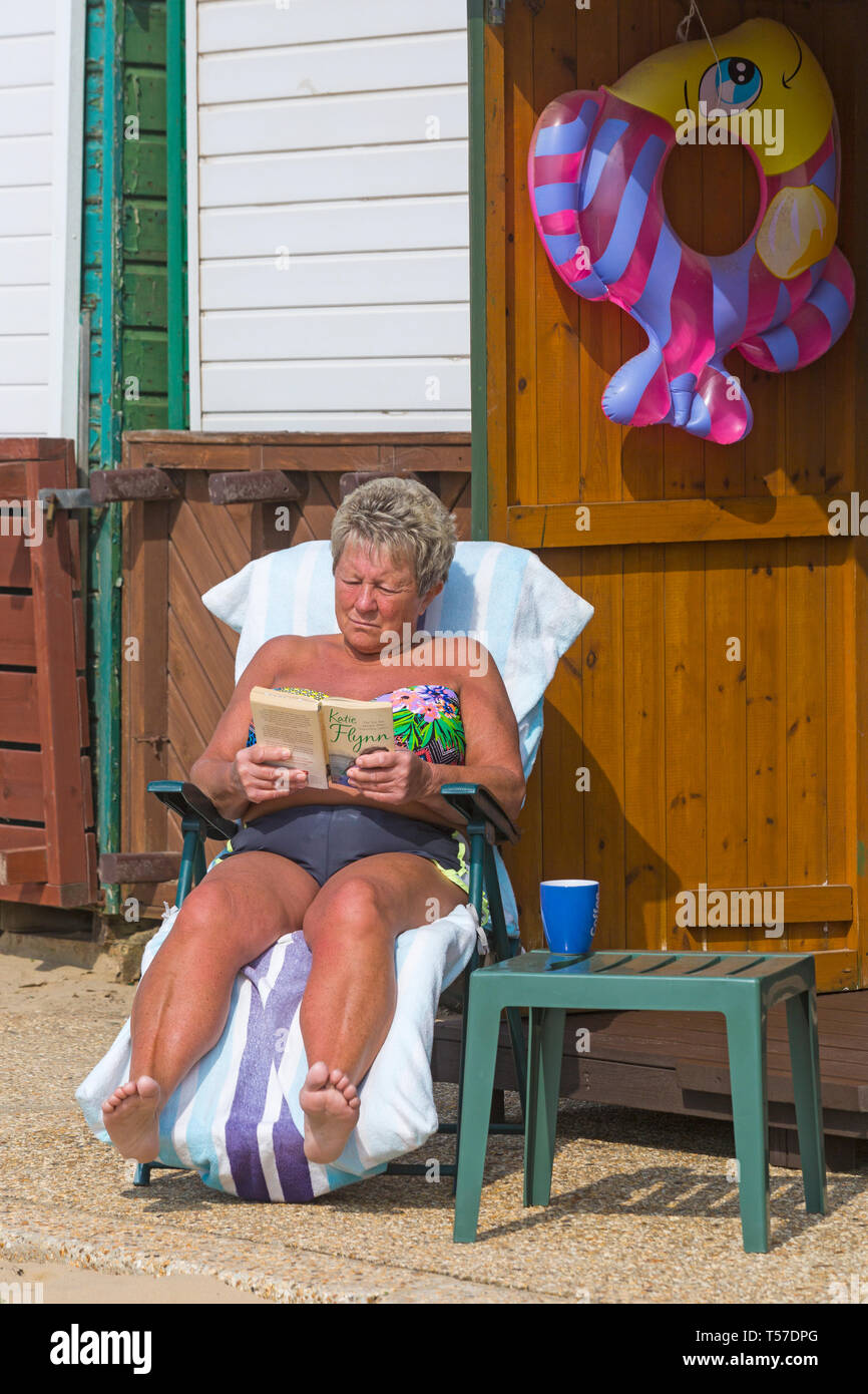 Bournemouth, Dorset, UK. 22nd Apr, 2019. UK weather: after a hazy start the glorious weather continues with hot and sunny weather, as beachgoers head to the seaside to enjoy the heat and sunshine at Bournemouth beaches on Easter Monday before the weather changes and the return to work. Woman reading Katie Flynn paperback book Sunshine & Shadows while sunbathing at beach hut. Credit: Carolyn Jenkins/Alamy Live News Stock Photo