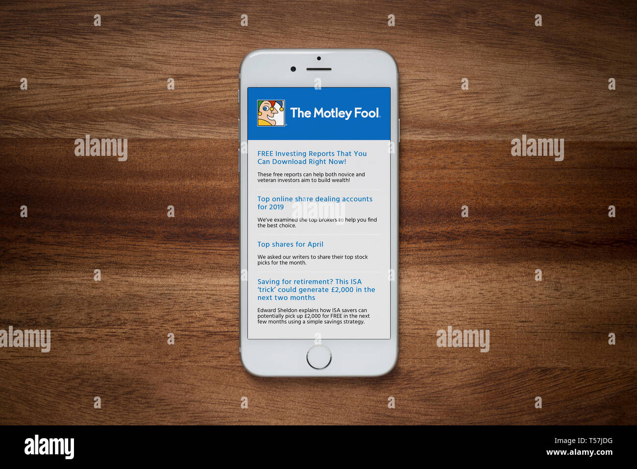 An iPhone showing The Motley Fool website rests on a plain wooden table (Editorial use only). - Stock Image