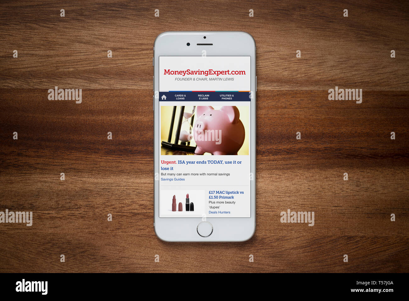 An iPhone showing the Money Saving Expert website rests on a plain wooden table (Editorial use only). - Stock Image