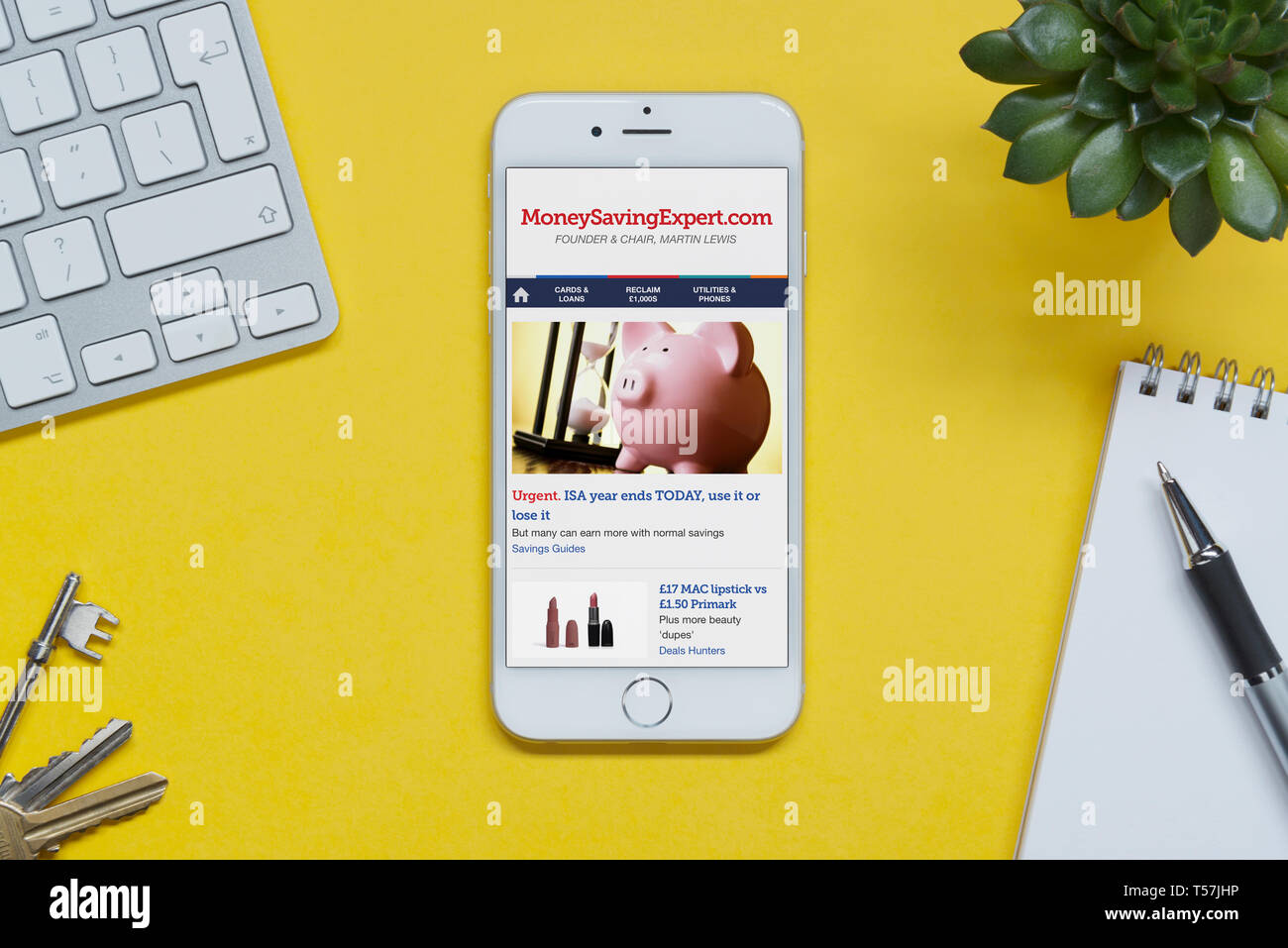 An iPhone showing the Money Saving Expert website rests on a yellow background table with a keyboard, keys, notepad and plant (Editorial use only). - Stock Image