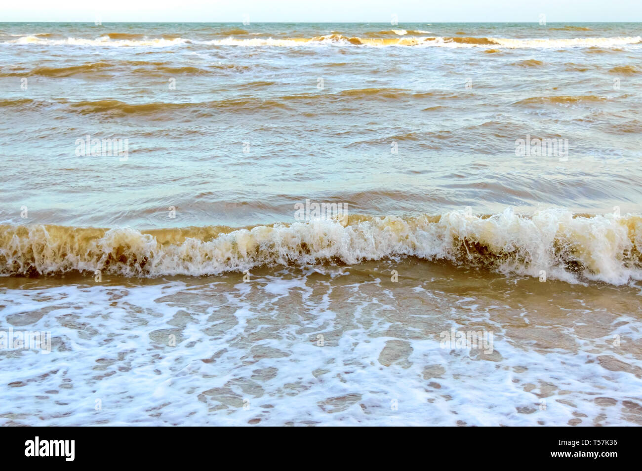 Waves on the shore. Sea wave close up on a sandy beach with sunlight. - Stock Image