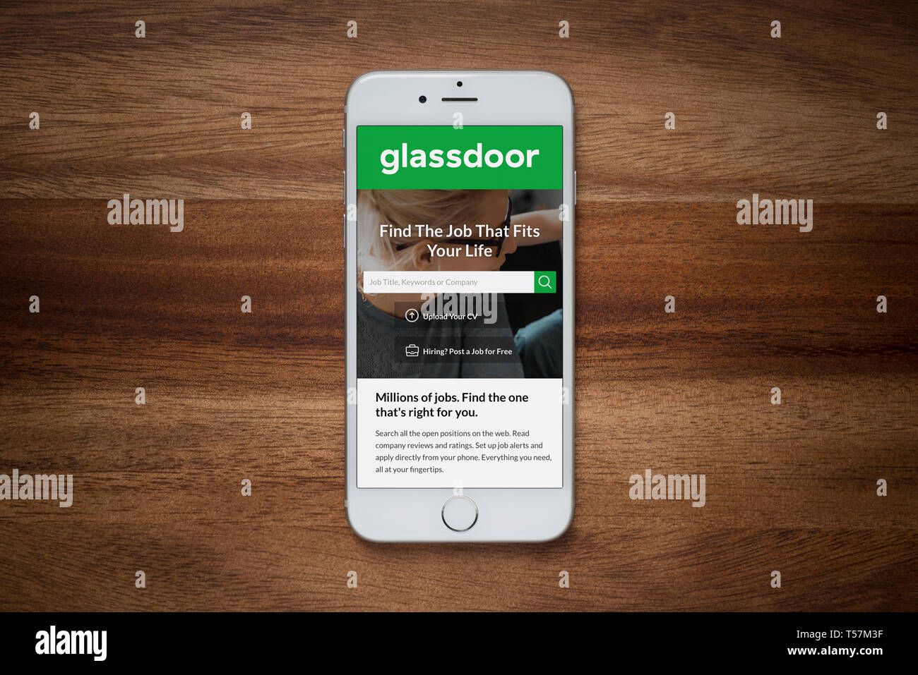 An iPhone showing the Glassdoor website rests on a plain wooden table (Editorial use only). - Stock Image