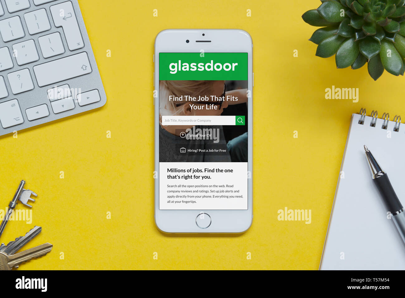An iPhone showing the Glassdoor website rests on a yellow background table with a keyboard, keys, notepad and plant (Editorial use only). - Stock Image