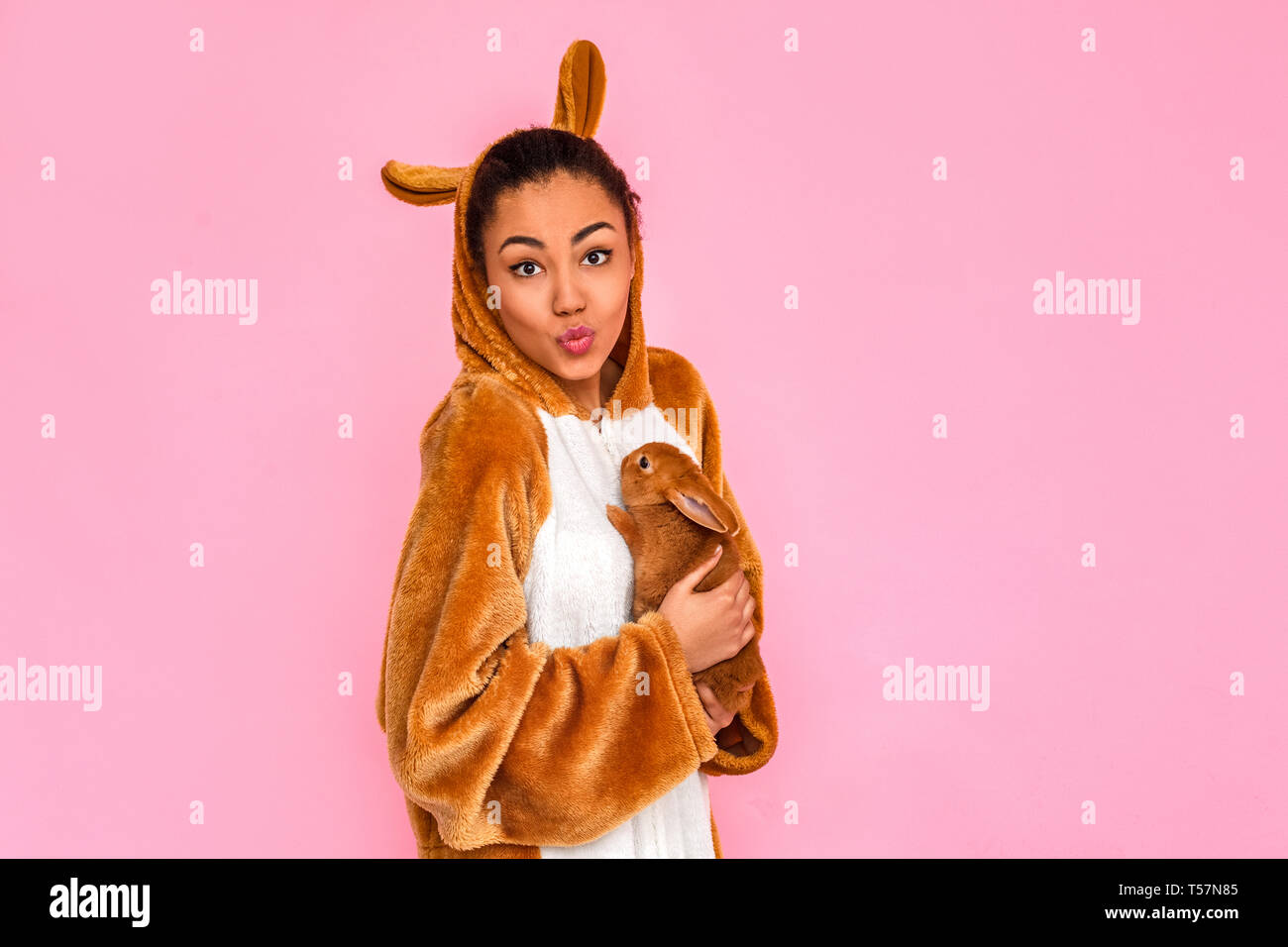 Young woman in bunny kigurumi standing isolated on pink background holding little rabbit looking camera pouting lips cute - Stock Image