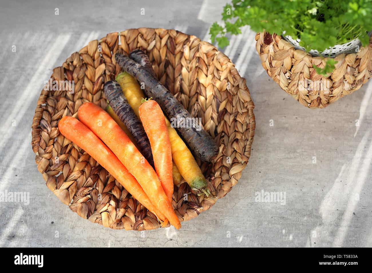 Colorful carrots, yellow, orange and purple.  Basket with vegetables on a kitchen counte Stock Photo