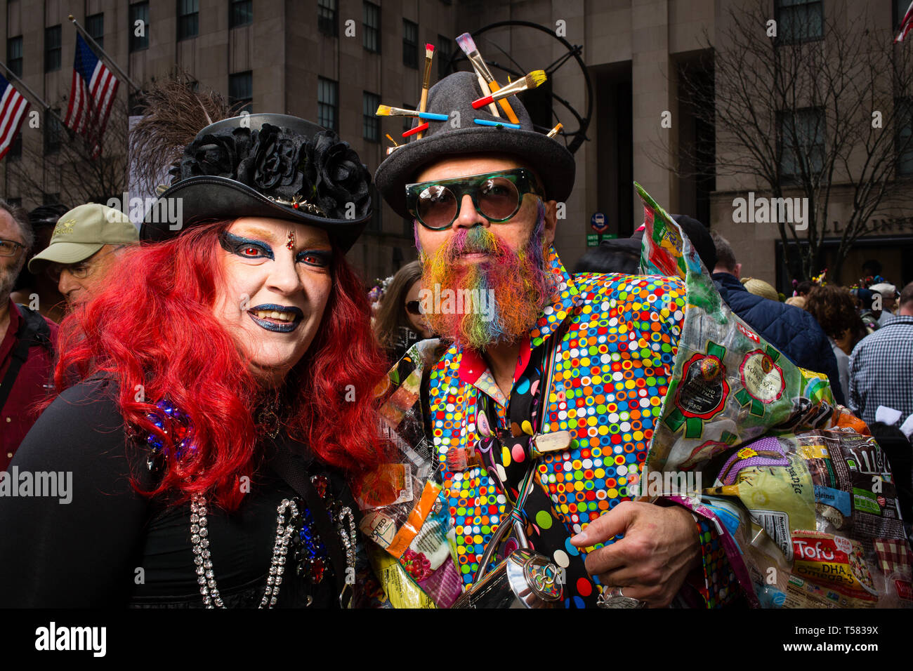 New York, NY - 21 April 2019. A woman with bright red hair and a black hat trimmed with black flowers next to a man with a hat bristling with artist's - Stock Image