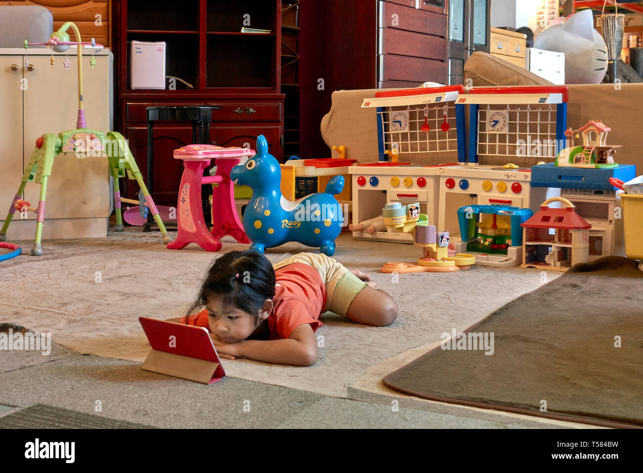 Young girl engrossed with her modern Ipad and ignoring her traditional toys. Concept of old v new. - Stock Image