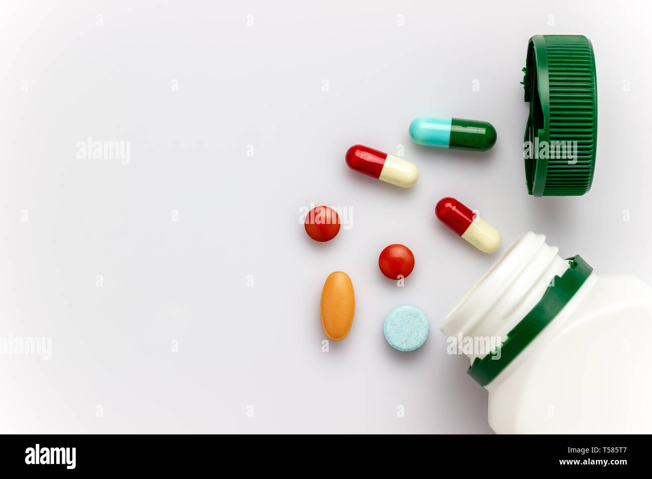 Multicoloured capsules with white medicine bottles and green caps on white background. Copy space for text or articles. Concepts of health and medicin Stock Photo