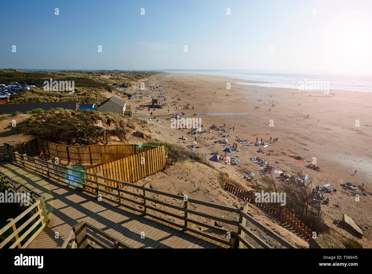 Tourists on Saunton Sands beach in North Devon during Easter 2019 heat wave with board walk in foreground - Stock Image