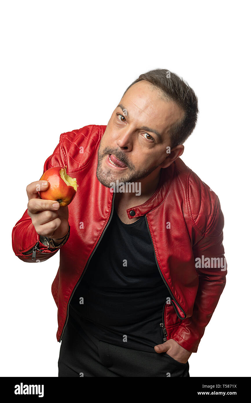 a stylish person is grimacing and holding an apple in his hand - Stock Image
