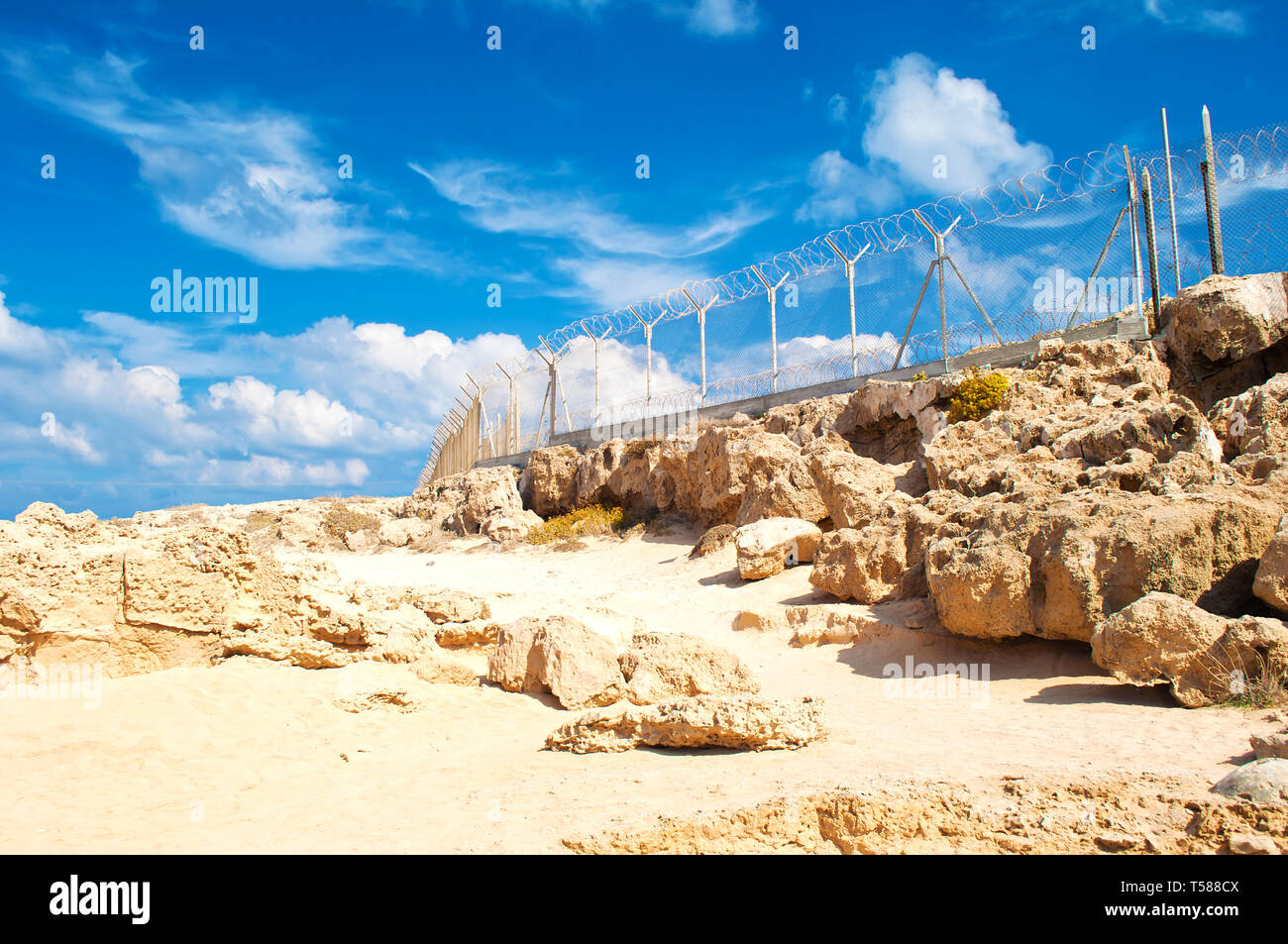 Military fence from barbed wire on a barren terrain with many rock boulders on a warm day in fall - Stock Image