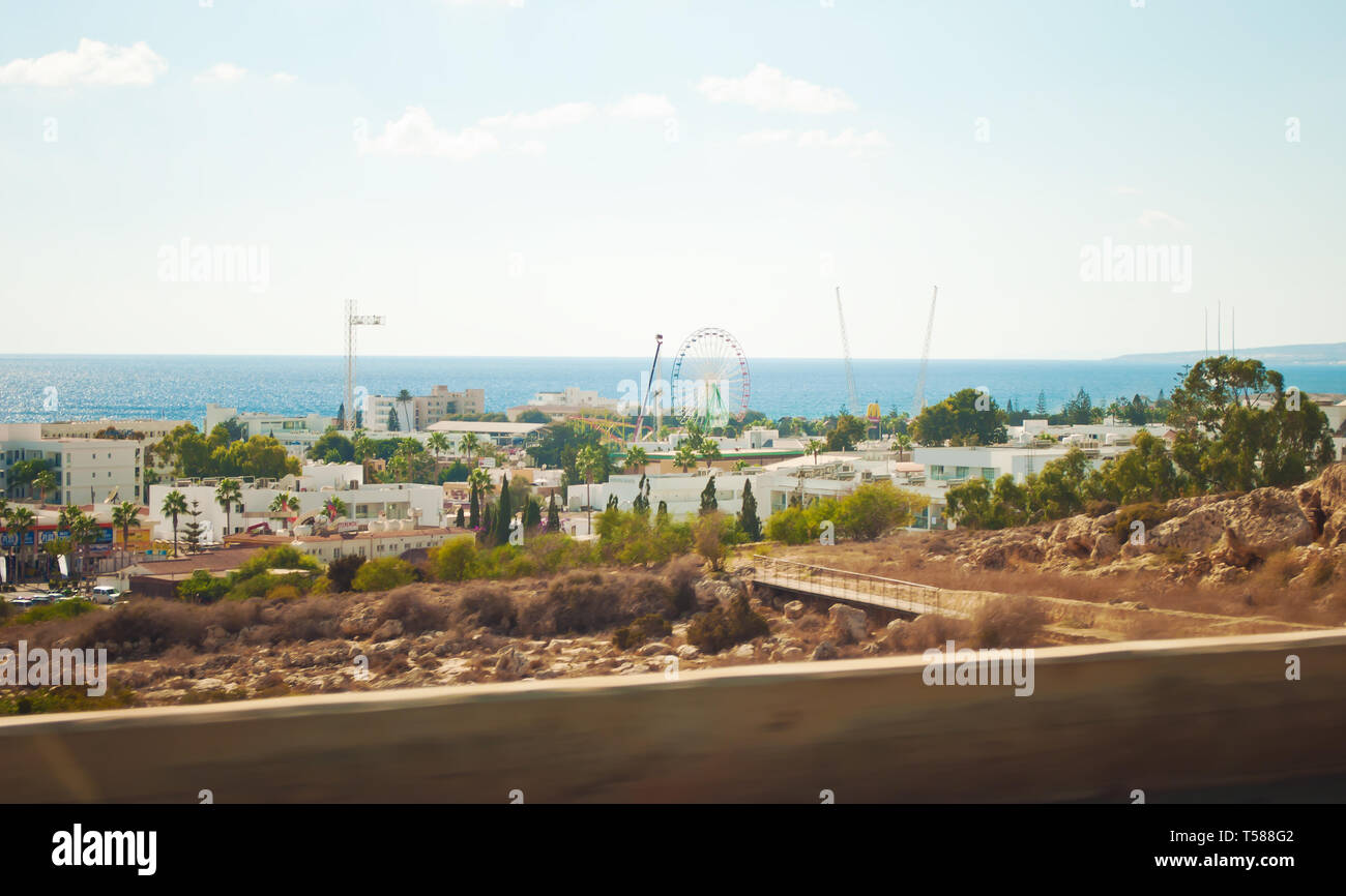 A big Ferris wheel among many white villas and palm trees in Agia Napa, Cyprus. Vast blue sea on the horizon. Warm day in autumn Stock Photo