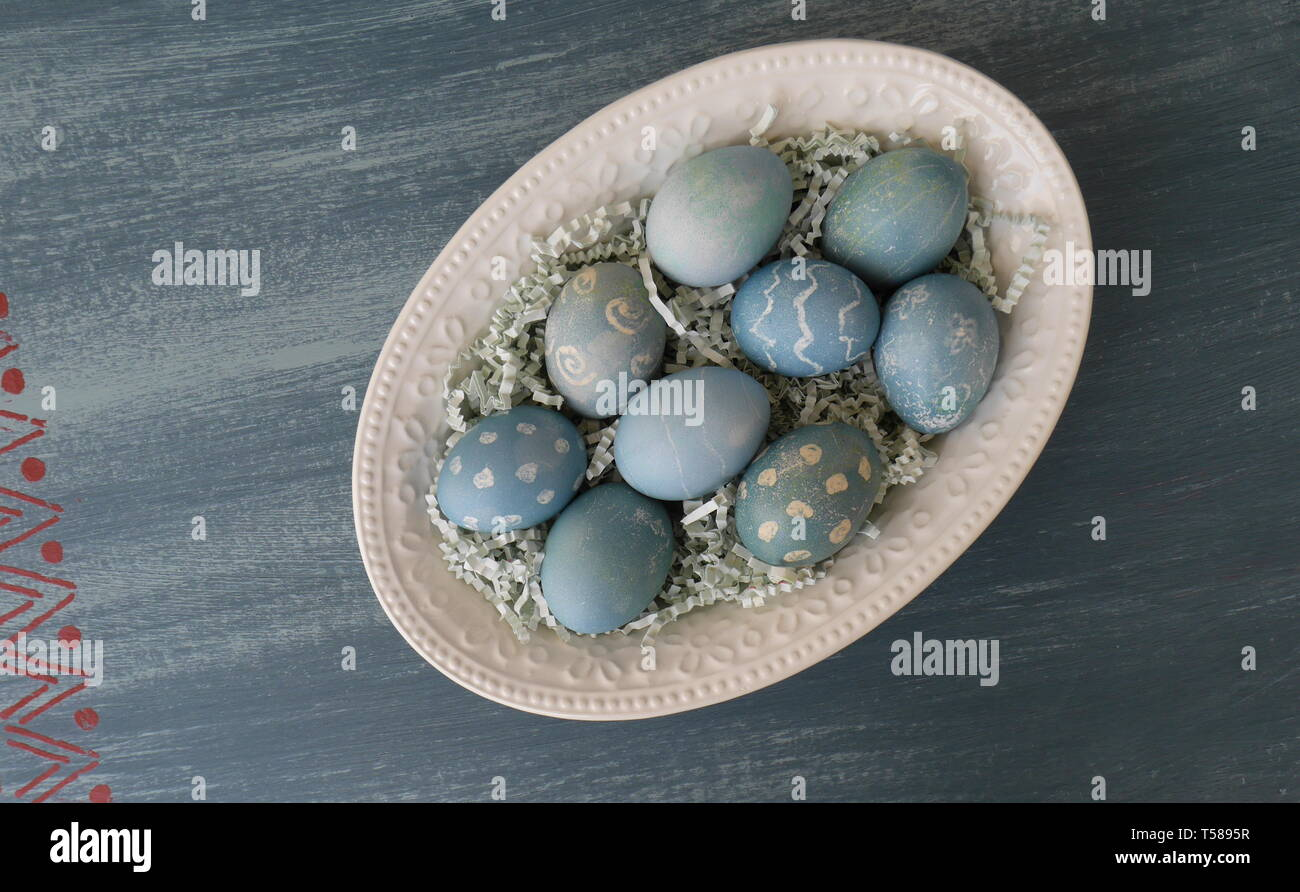 Painted Easter eggs, coloured with dye from red cabbage, on a chalk painted blue distressed wood table - Stock Image