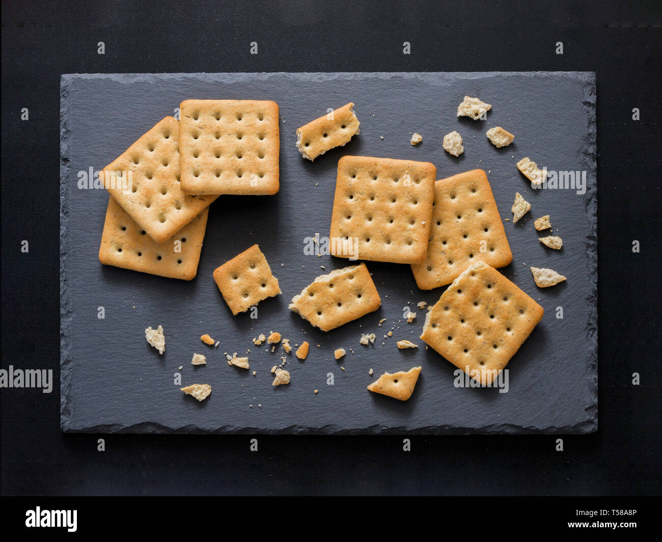 Square crackers with pieces and crumbs on slate gray background. Dry salt cracker cookies with fiber and dry spices. Top view or flat lay. - Stock Image