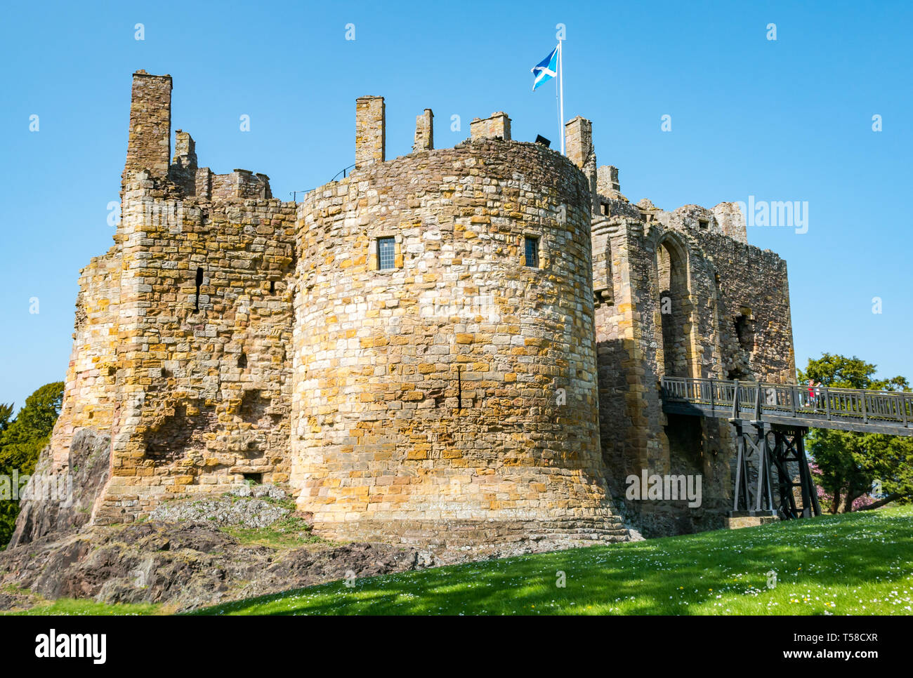 Medieval 13th century Dirleton Castle fortress with moat, popular visitor attraction, East Lothian, Scotland, UK with blue sky - Stock Image