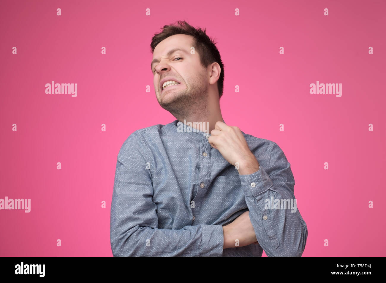 Frowning young businessman choking trying to put off his shirt. - Stock Image