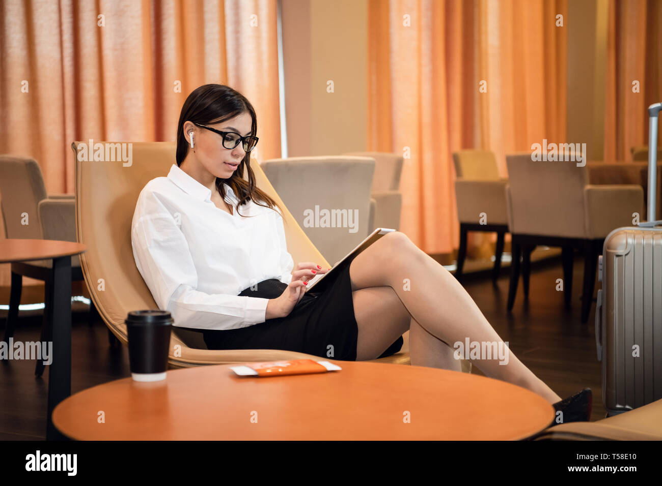 Confident businesswoman listening music on her tablet computer while sitting in chair in airport business lounge - Stock Image