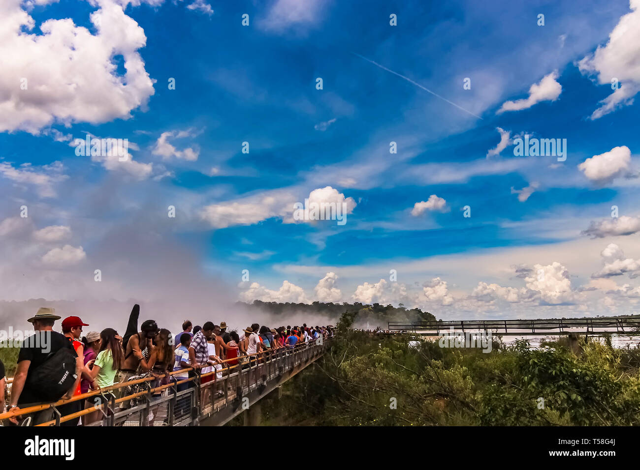 Misiones Province, Argentina - Jan 2015: Long queue of tourists on the metal walkway towards the cliff of the Devils Throat at Iquazu Falls - Stock Image