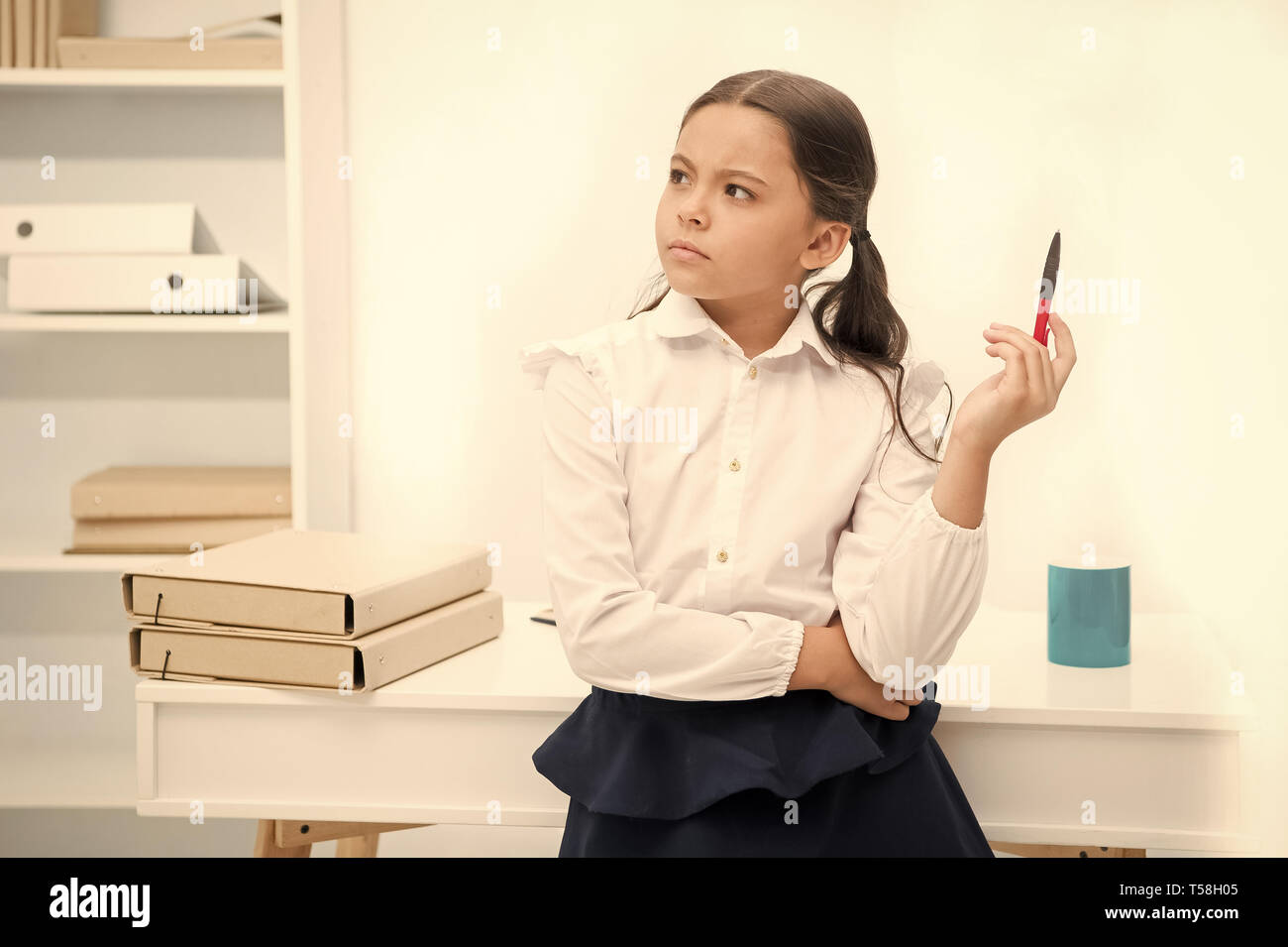 Let me think. Child girl wears school uniform standing with remembering face expression. Schoolgirl smart child looks thoughtful white interior background. Girl try to remember her knowledge. - Stock Image