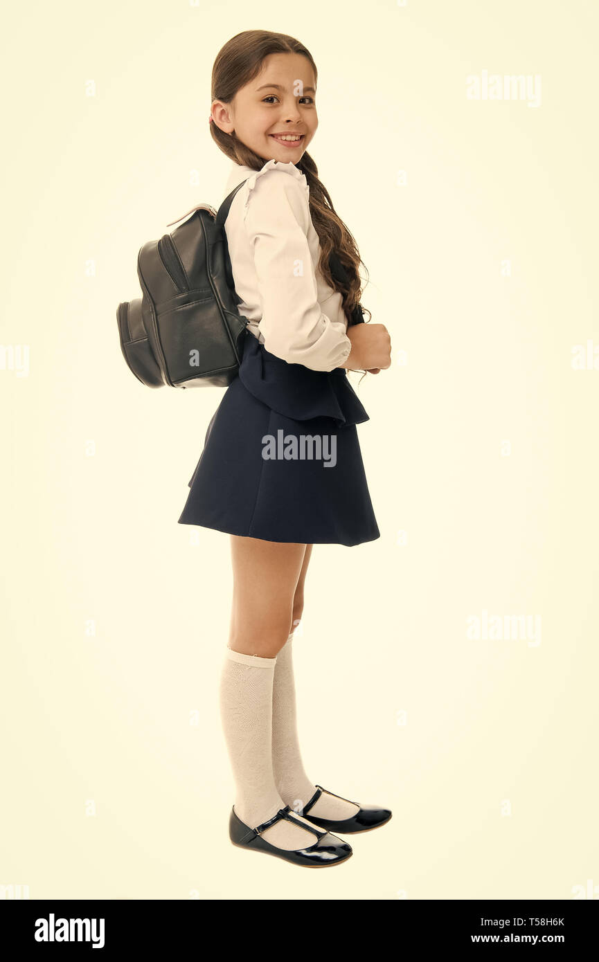 Right and wrong ways to wear backpack to prevent pain. Learn how fit backpack correctly for school. Schoolgirl cute in formal uniform wear backpack. School backpack concept. Follow these tips. - Stock Image