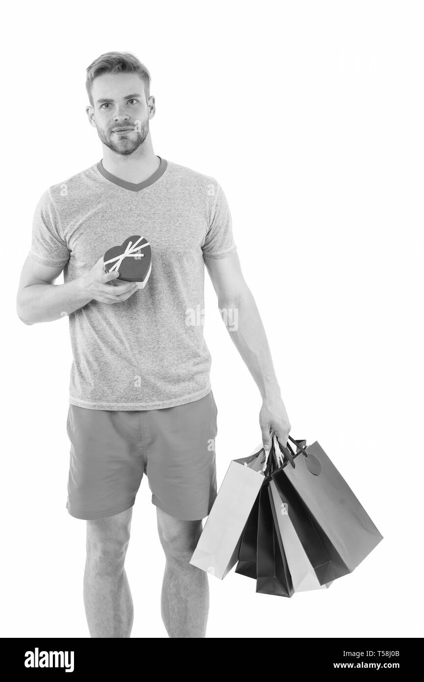 Buy gift for her. Man handsome unshaved macho hold bunch shopping bags. Buy gifts concept. Guy shopping before holidays. Shopping discount sale season. Man carry paper shopping bags with items. - Stock Image