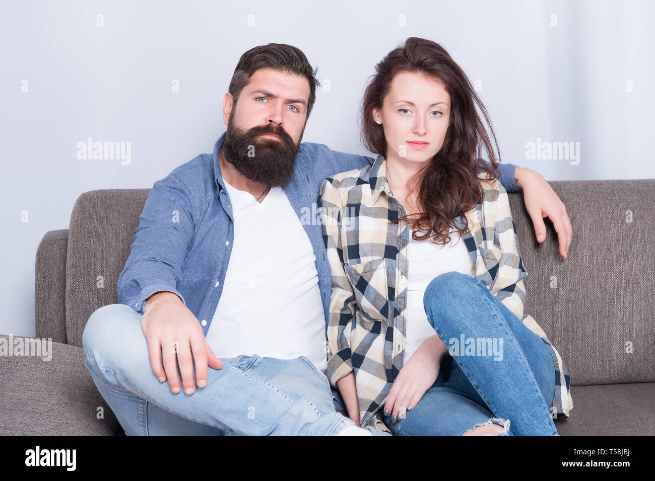 Regular couple relaxing on couch. Session at family psychotherapist. Couple in love hug looking at camera. Family relations. Family leisure. Happy and healthy relations. Bearded man and pretty girl. Stock Photo