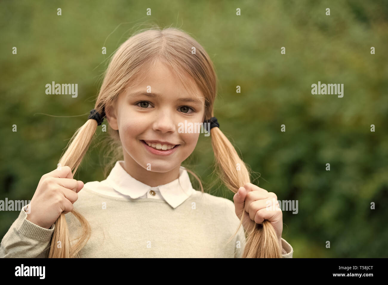 Girl happy smile with blond hair ponytails on green nature background. Hairstyle for cute schoolgirl. She looks tidy and cute with those ponytails. Easy tips create daily hairstyle. - Stock Image