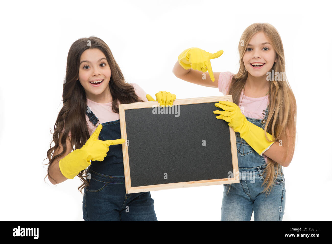 A little help for keeping things tidy. Adorable tidy schoolgirls in rubber gloves pointing at tidy blackboard. Primary school children keeping their school supplies clean and tidy, copy space. - Stock Image
