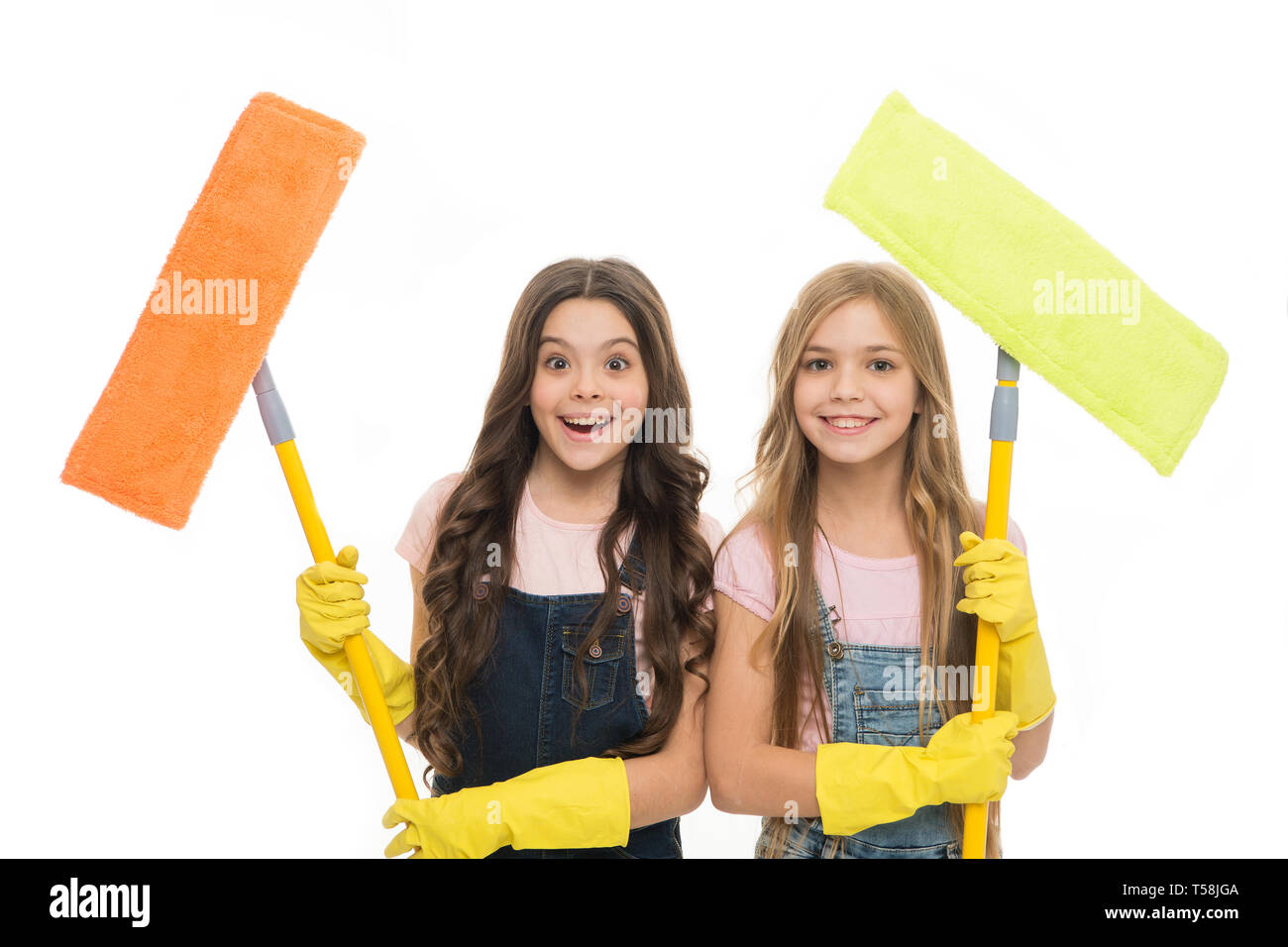 Adorable clean freaks. Cute girls holding mops for cleaning floor. Small cleaning ladies. Little cleaners with modern cleaning tools. Sanitation and cleaning service. - Stock Image