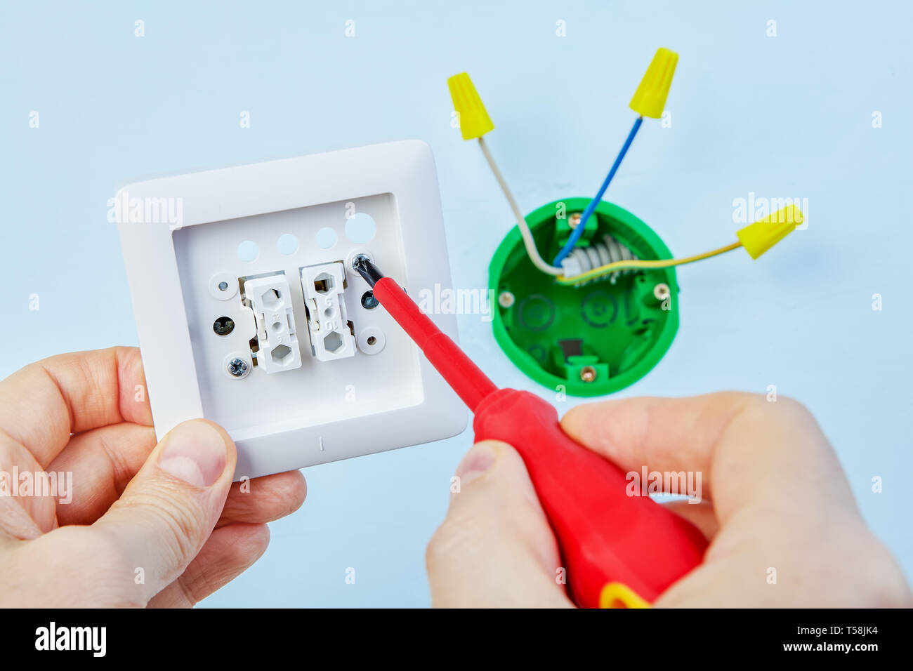 Electrician is installing new double light switch with help