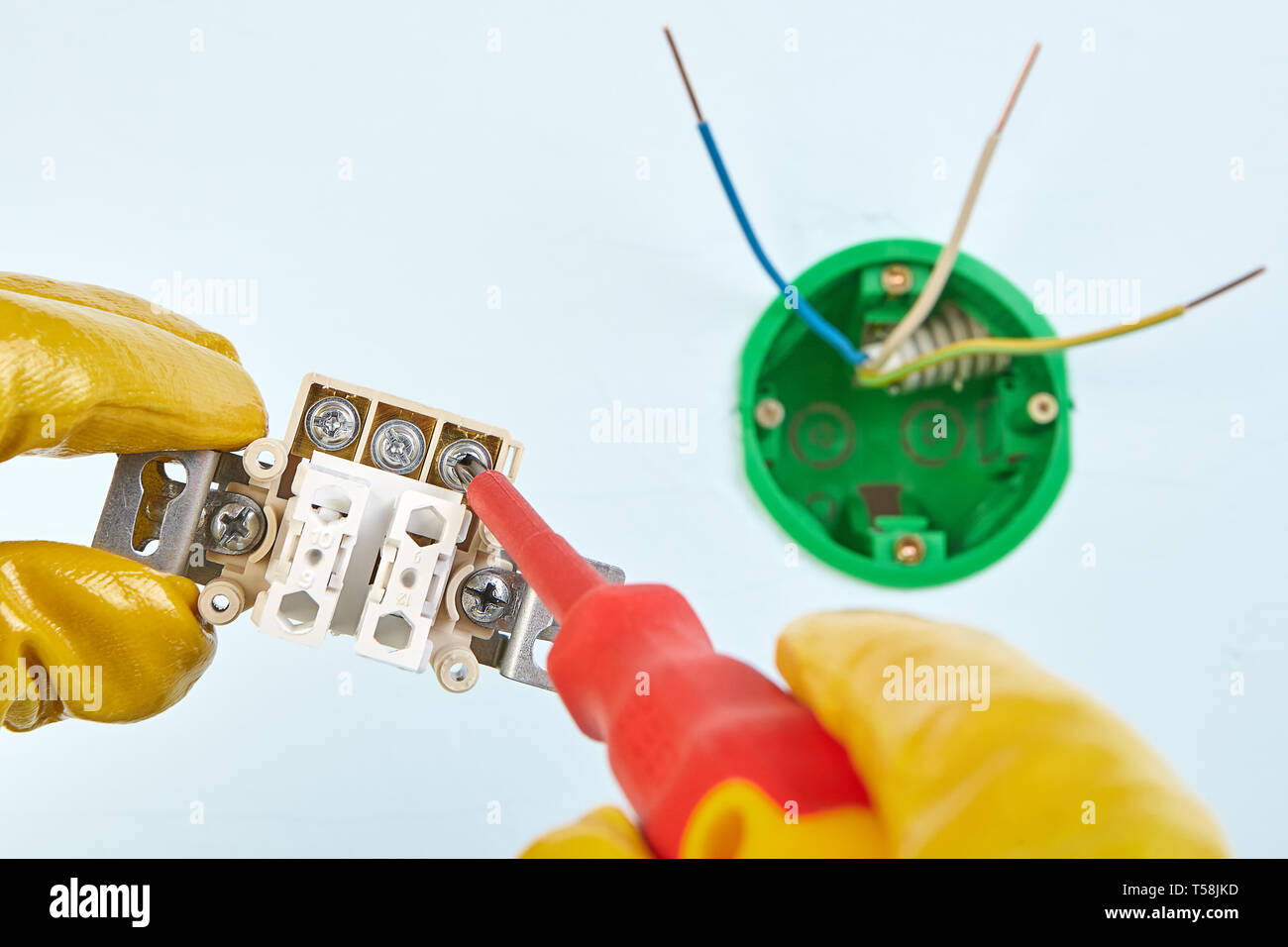 Electrician in yellow protective gloves is twisting in ... on