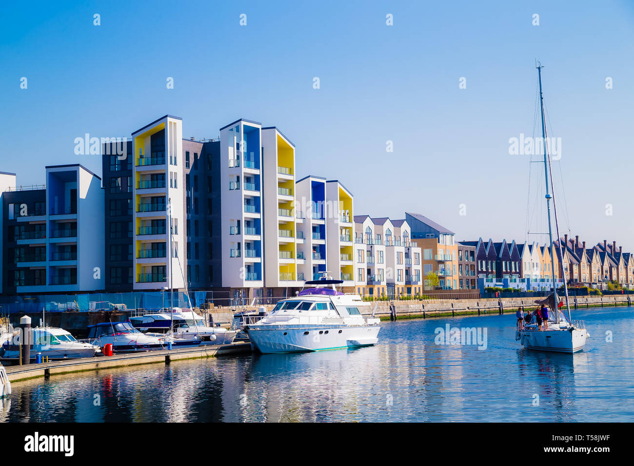 A yacht with a tall mast passes by luxury apartments on St
