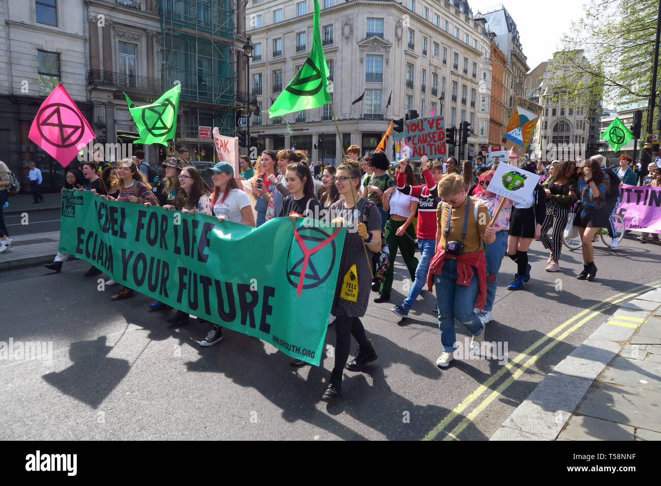 A group of Extinction Rebellion Youth protestors march around the south side of Trafalgar Square, central London. One of many marches against climate  Stock Photo