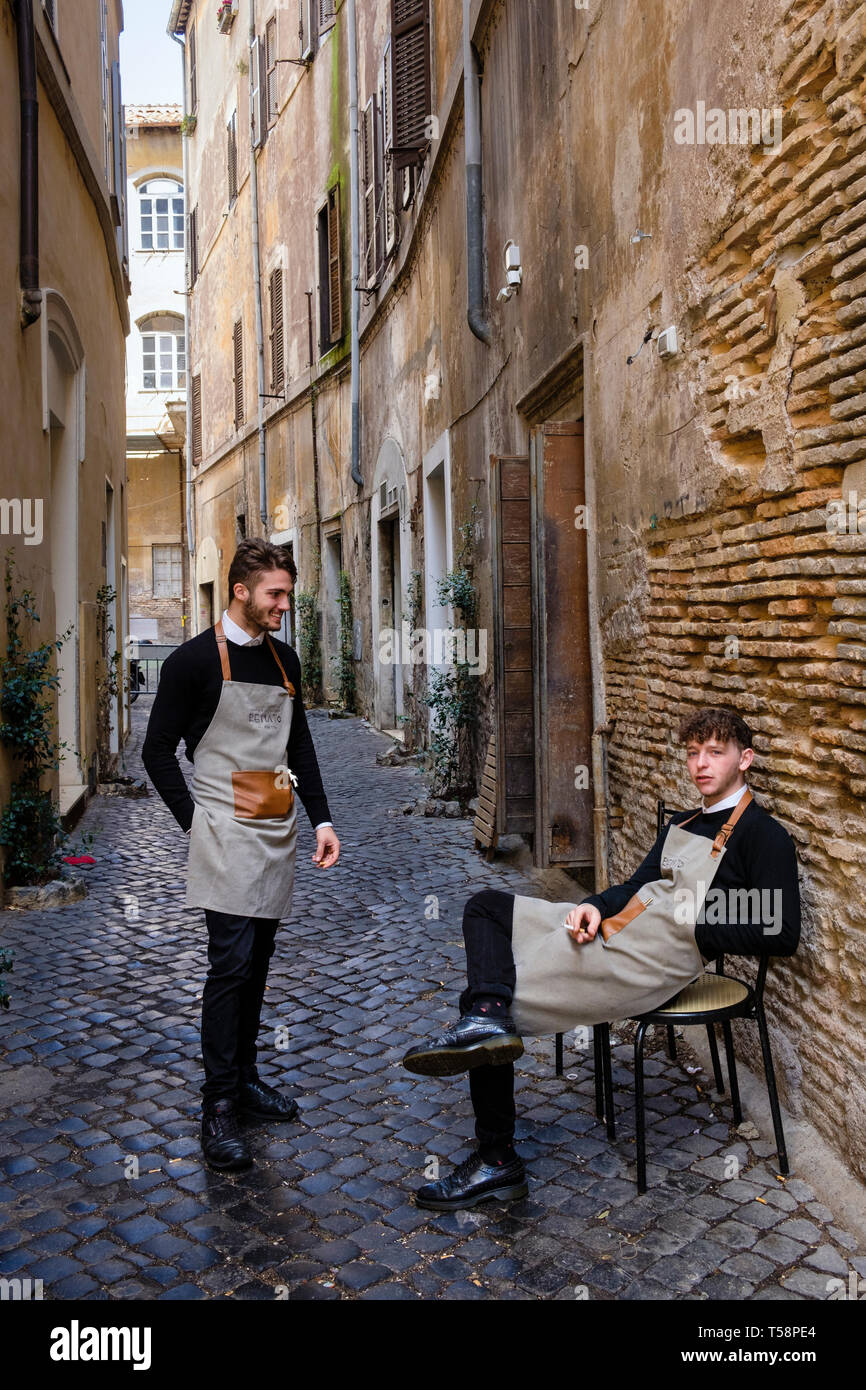 Restaurant waiters having a break in the Jewish Quarter, Rome, Italy - Stock Image