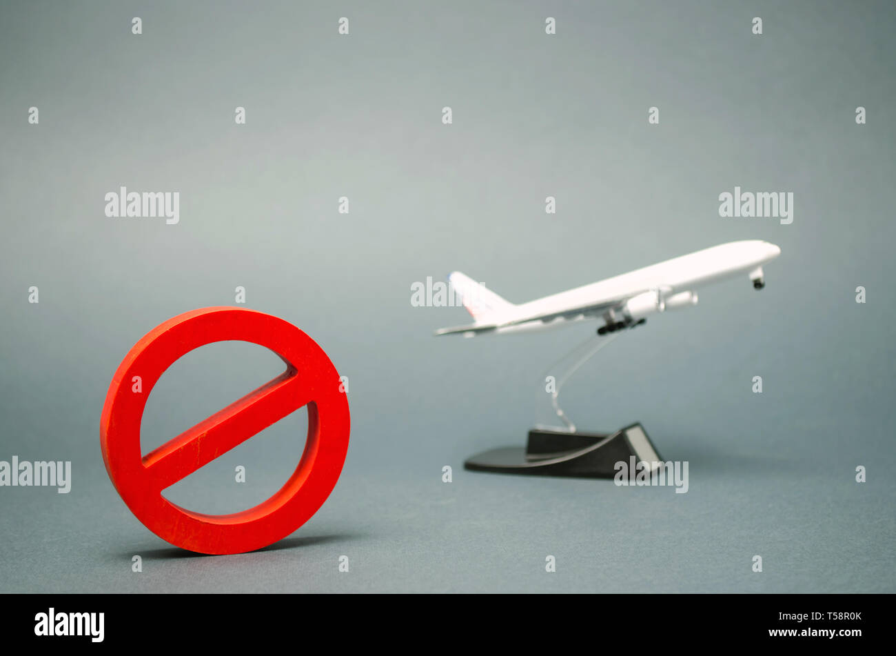 The sign of the ban and a miniature toy aircraft. Ban on flights of civil aircraft. Forbidden zone. Stop symbol. Bans on airport construction. Plane.  - Stock Image