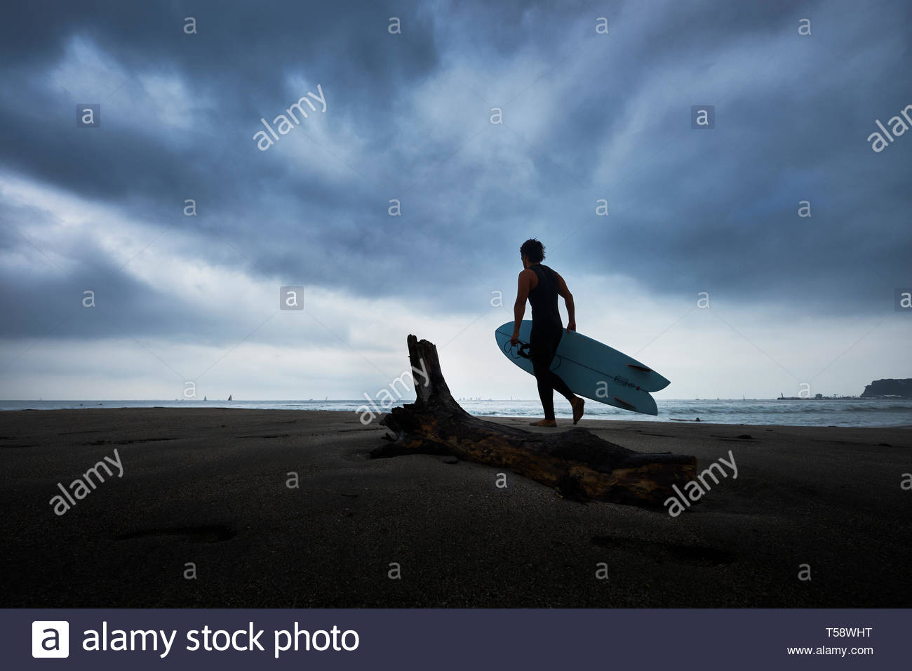 Surfer on the beach and dramatic sky in Inamuragasaki - Stock Image
