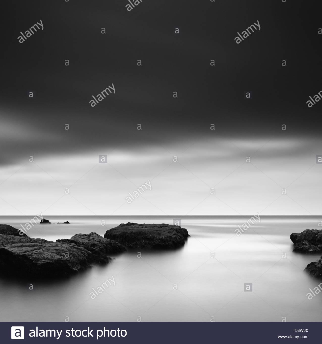 Long exposure of sea rocks and dramatic sky in Inamuragasaki, Kanagawa - Stock Image