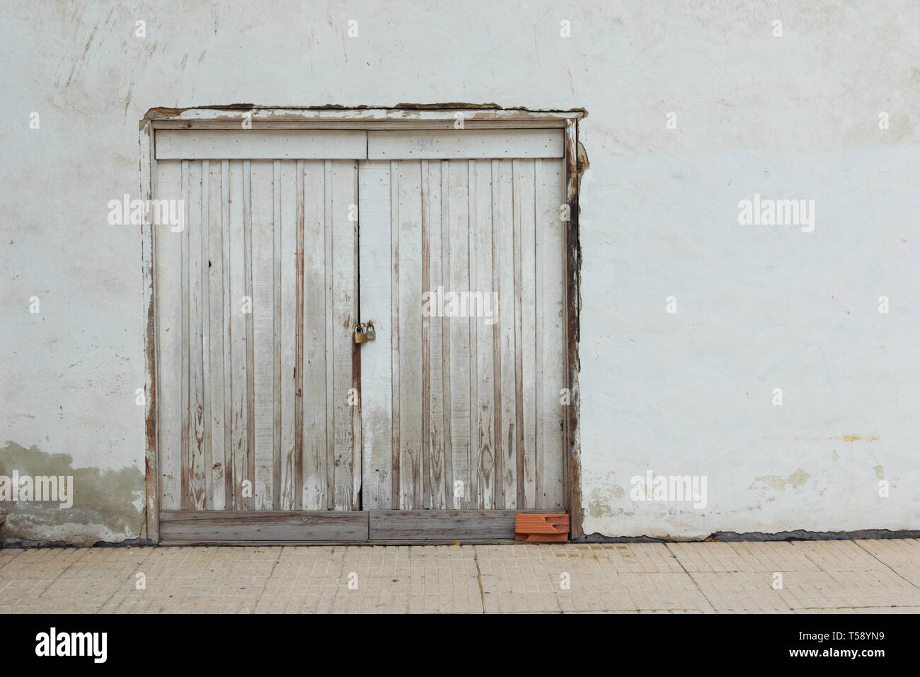 Old  white door on a white painted wall and a brown brick. - Stock Image