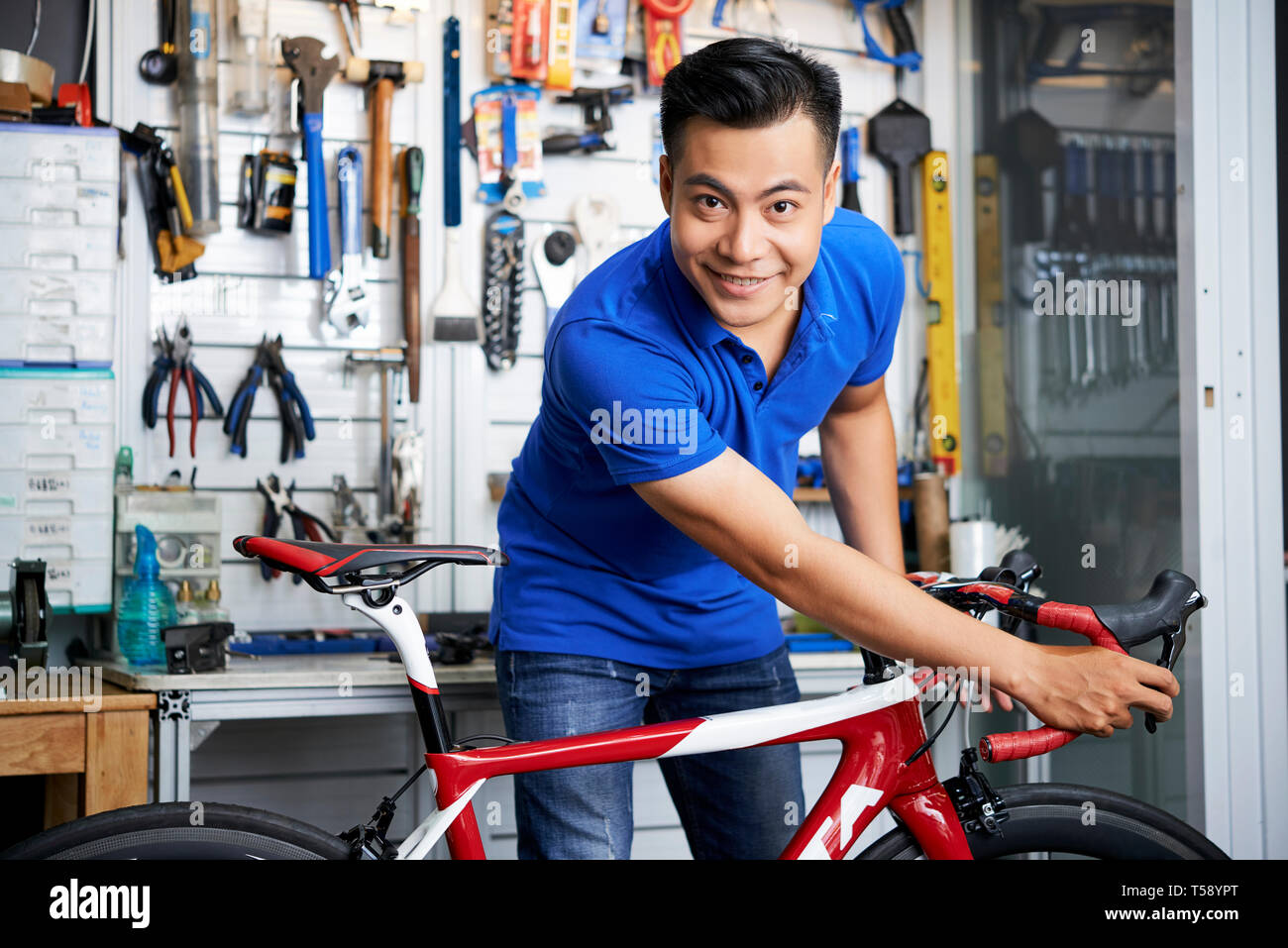 Mechanic with bicycle in workshop - Stock Image