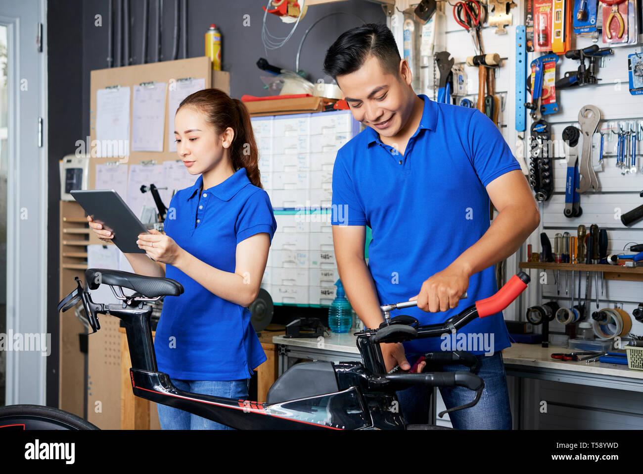 People repairing the bike in team - Stock Image
