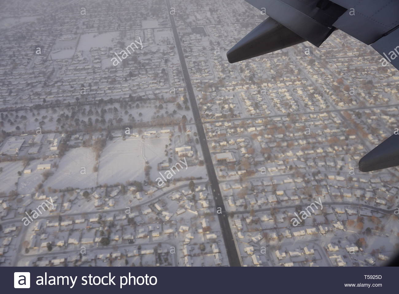 Delta airplane wing from airplane window above Salt Lake City houses covered in snow in the winter. Roads and houses from the airplane. - Stock Image