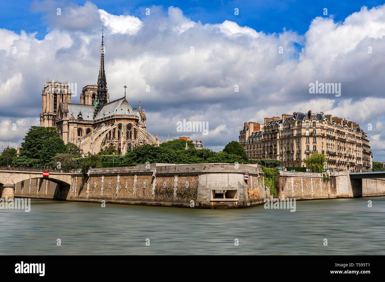 Famous Notre-Dame de Paris cathedral and typical Parisian building under beautiful sky as seen from Seine river. - Stock Image