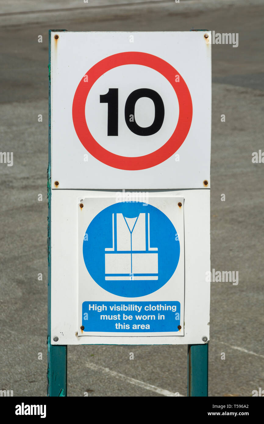 10 MPH vehicle speed sign with High Viz clothing safety sign. Health and safety at work concept. - Stock Image