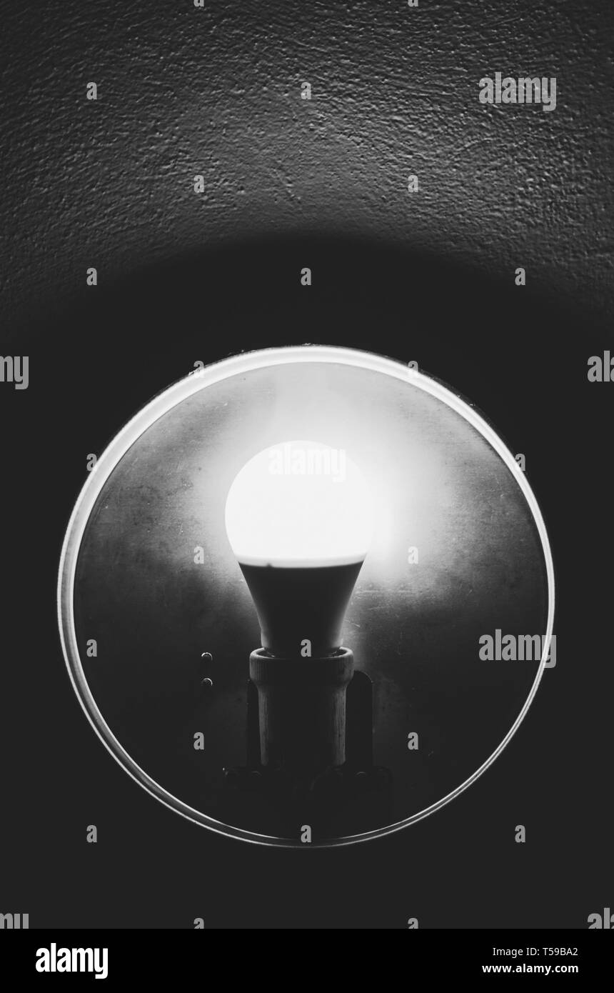 isolated underexposed old bulb light in black and white - Stock Image