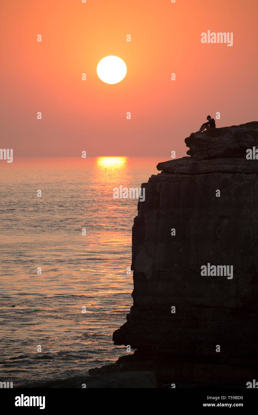 A young man sitting on top of the famous attraction of Pulpit Rock on Portland Bill on the tip of the Isle of Portland watching the sun setting after  - Stock Image
